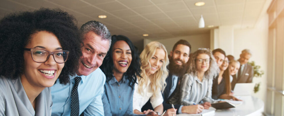 Cheerful multiracial colleagues looking at camera in office